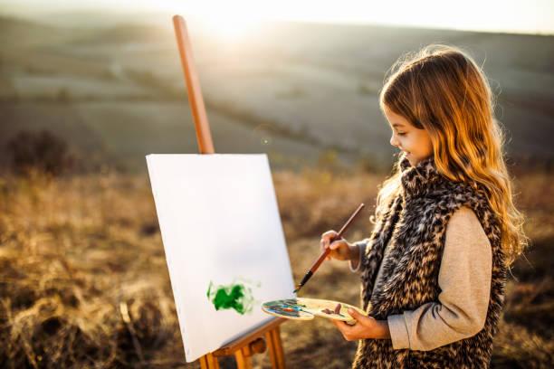 kleine kreative mädchen malen auf dem feld. - naive malerei stock-fotos und bilder