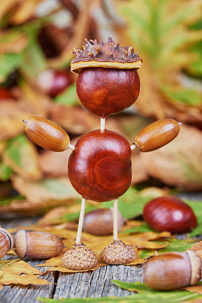 Small creature made of chestnuts and acorns. Autumnal decoration stock photo