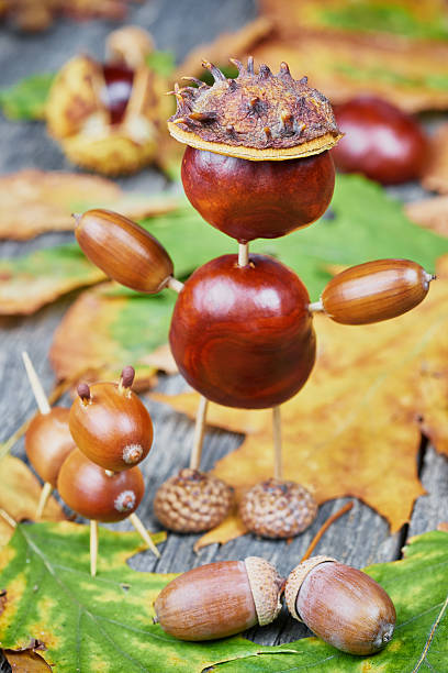 Small creatures made of chestnuts and acorns. Autumnal decoratio stock photo