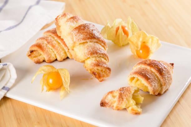 kleines croissant mit physalis früchte - portugiesische desserts stock-fotos und bilder