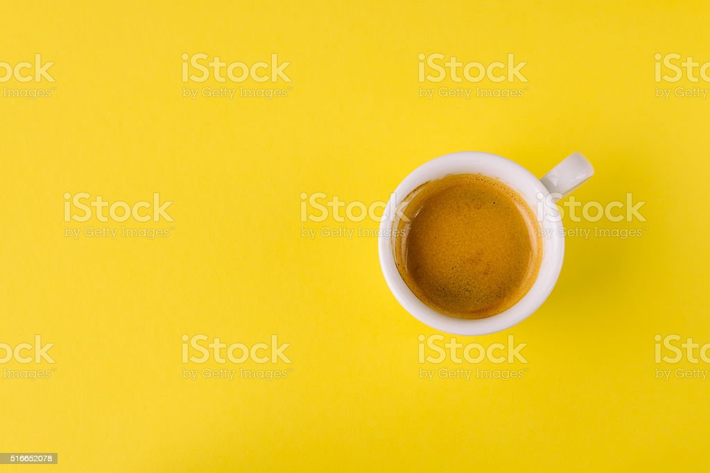 Small cup of coffee on bright yellow background