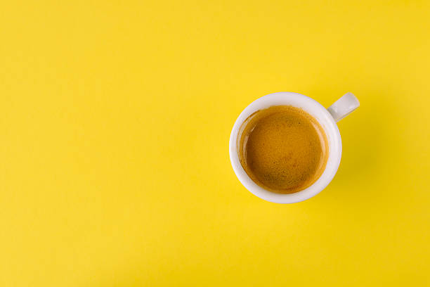 Small cup of coffee on bright yellow background stock photo