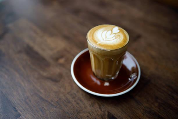 kleine Tasse Kaffee mit Herzmuster Schaum auf Holztisch – Foto
