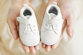 """Tiny white baby shoes in man""""u2019s hands. Closeup. Baby, pregnancy, parenting concept."""