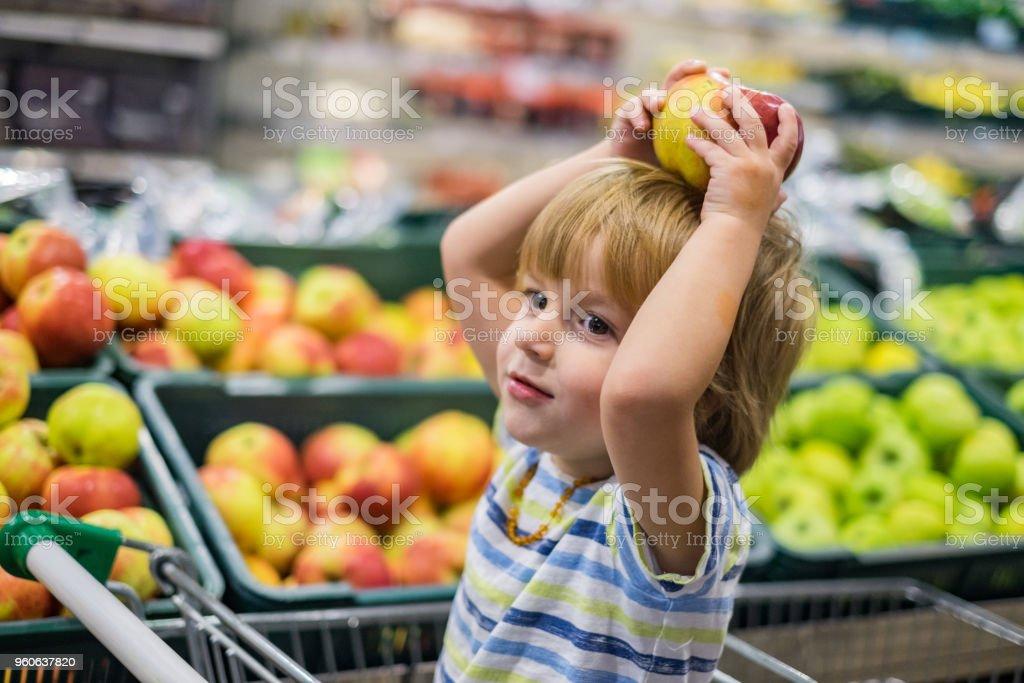 Pequeno garoto bonito, jogando com a apple na loja - foto de acervo