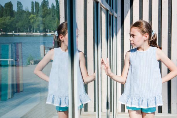 klein, schattig meisje kijkt naar haar reflectie zonnige dag - lichaamsbewustzijn stockfoto's en -beelden