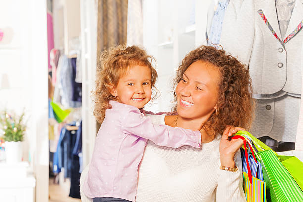 kleines süßes mädchen mit ihrer schönen mutter einkaufen - mutterkleiderschrank stock-fotos und bilder
