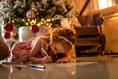 istock Small cute girl writing letter to Santa at home 1194180063
