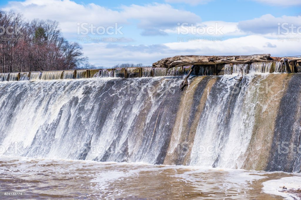 Small dam with running water fall in Accotink park in Fairfax, Virginia stock photo