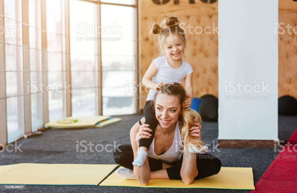 A small daughter sits at her mother's back stock photo