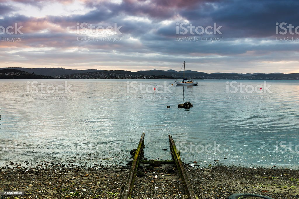 Small Delapidated Boat Ramp and Overcast Sunrise on Derwent Estuary stock photo