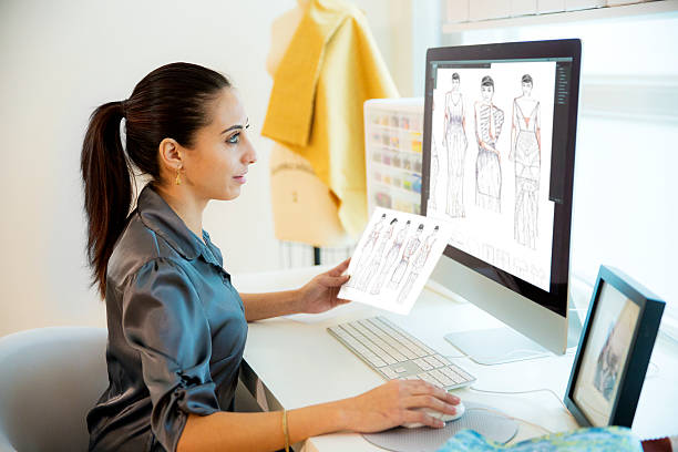 Small Design Business Portrait of businesswoman and fashion designer  in design studio working at computer workstation designing fashion illustrations holding fabric samples and mannequin in the background. illustrator stock pictures, royalty-free photos & images