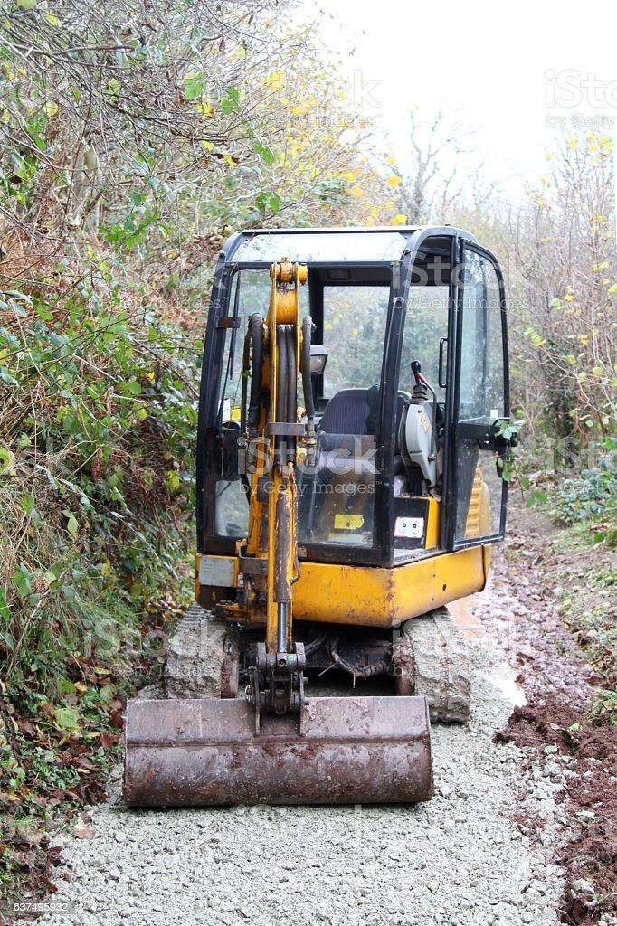 small digger machine on path stock photo