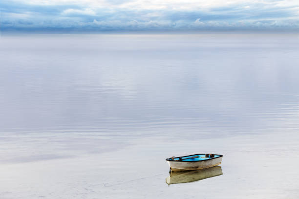 Small Dinghy Moored in a Calm Bay as a Storm Passes on the Horizon stock photo
