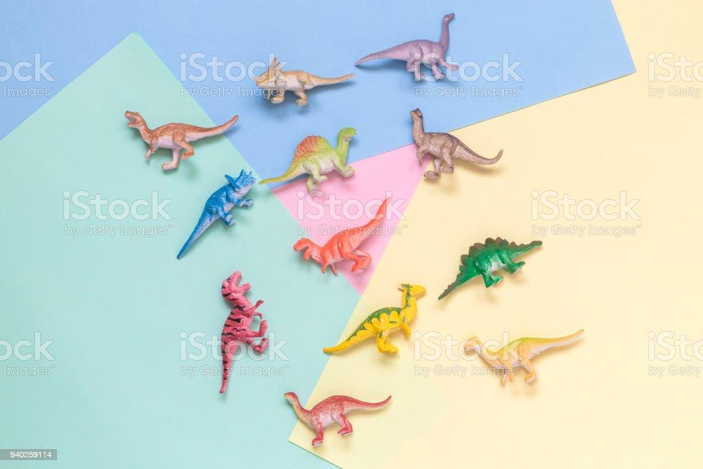 Pequenos dinossauros no conceito minimalista de plano de fundo multicolorido. - foto de acervo