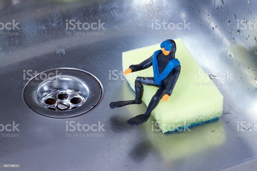 small diver sitting in a steel sink on the sponge stock photo