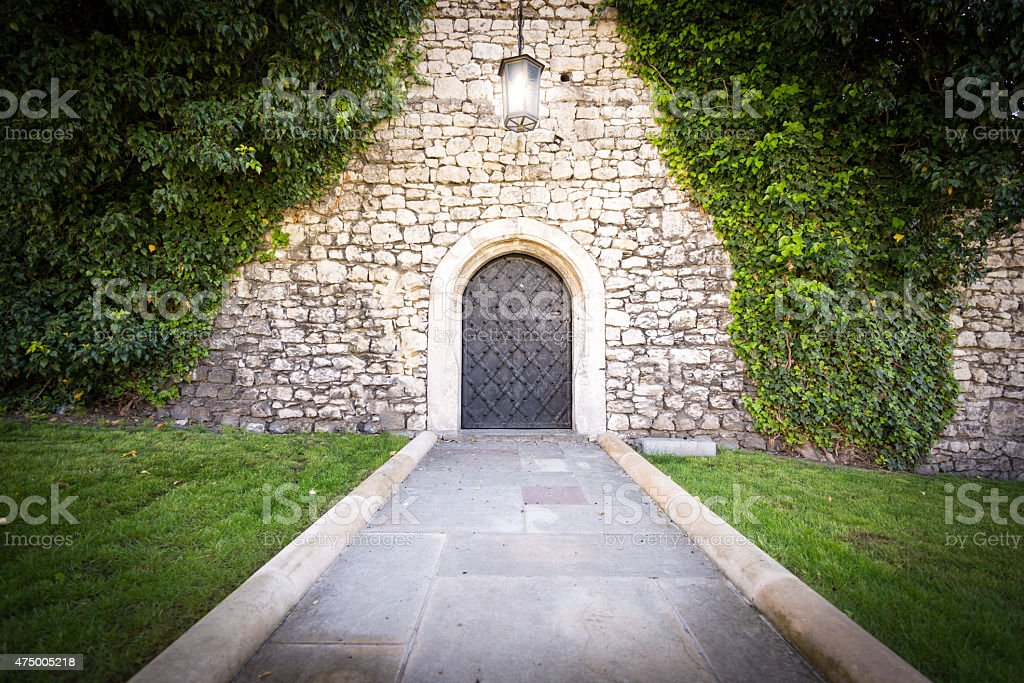 Small door at stone wall of old castle. stock photo