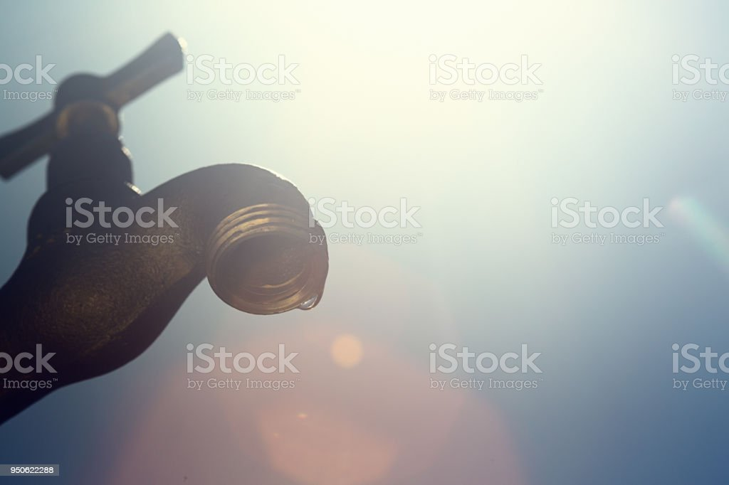 Small drops of water from a faucet symbolize drought or water wastage stock photo