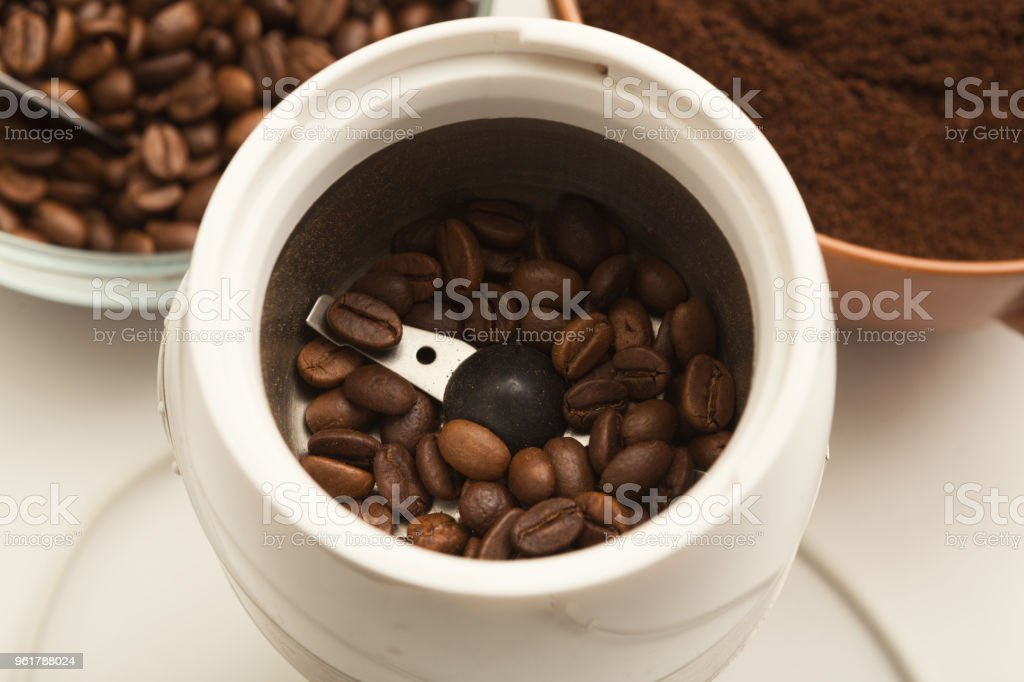 Small electric coffee mil with roasted beans stock photo