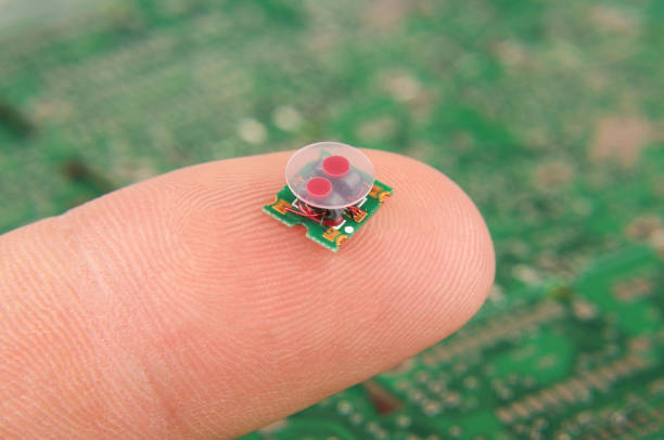 small electronics component rf transformer on human finger - ingrandimento foto e immagini stock