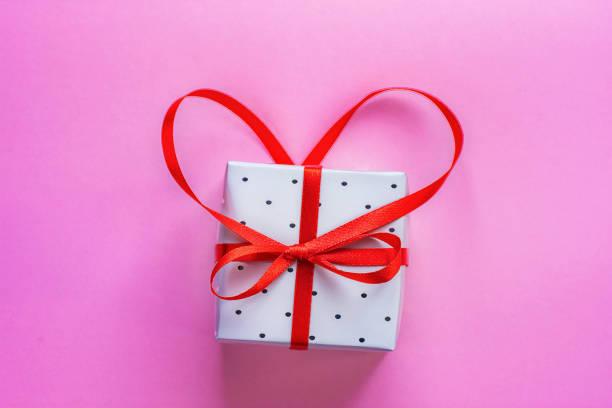 kleine elegante geschenkbox mit schleife in herzform auf rosa hintergrund mit roten band gebunden. valentinstag-grußkarte hochzeit muttertag geburtstag. kopieren sie raum. poster banner vorlage. - originelle geburtstagsgeschenke stock-fotos und bilder
