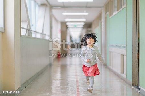 istock Small elementary girl running in hallways at school 1190422026