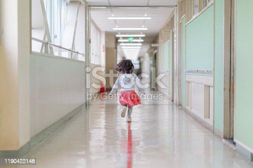 istock Small elementary girl running in hallways at school 1190422148