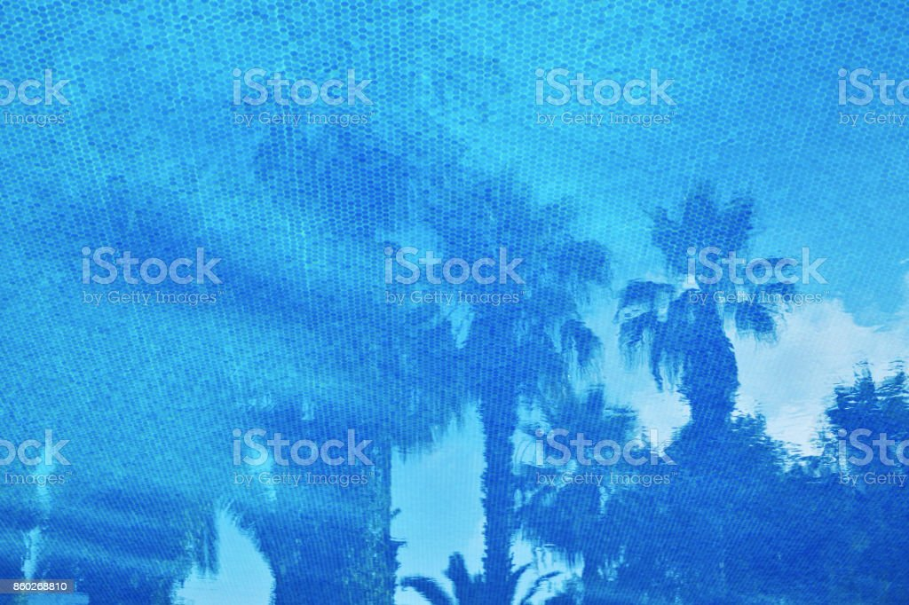 Small elements blue mosaic on the bottom of the pool pattern. Reflections of palm trees on the water surface. Travel background. Close up. stock photo