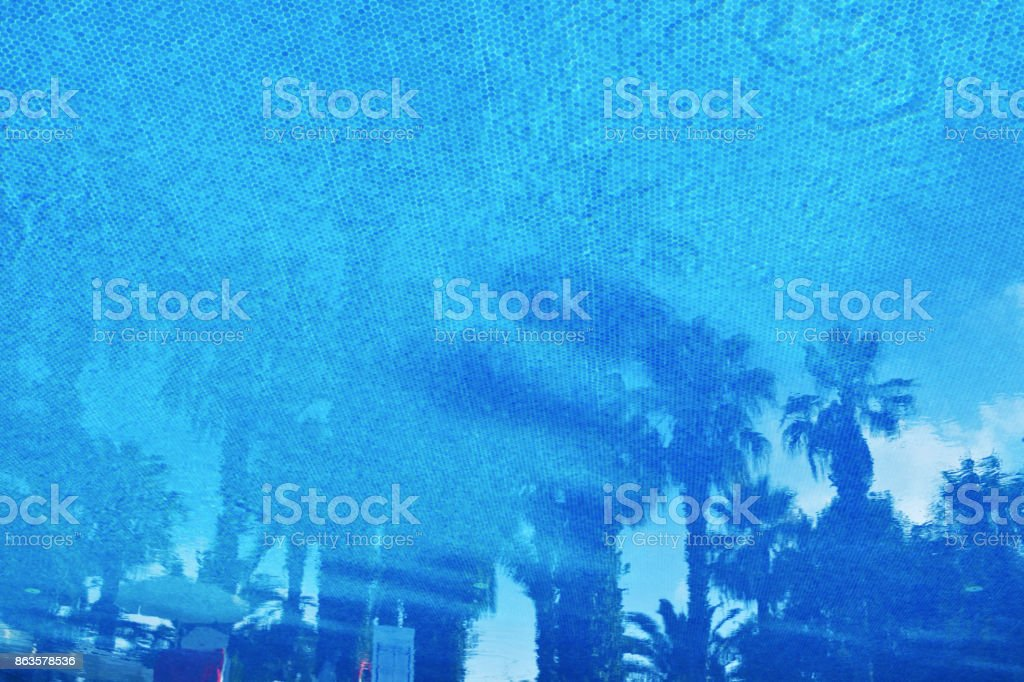 Small elements blue mosaic on the bottom of the pool pattern. Reflections of palm trees on the water surface. Travel background. Copy space. stock photo