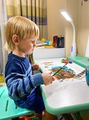 A small fair-skinned child draws with multi-colored paints at the table in the children's room.Children's creativity concept. Free space.Defocus light background.