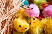 Fluffy pink, yellow, green and blue, small fake easter chicks and natural raffia nest material.