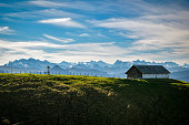 Small farm close to Chli Aubrig peak with beautiful views on majestic Alps in background in Switzerland