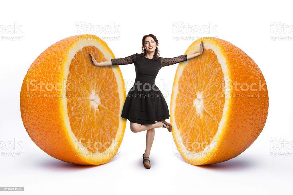 small female between halves of giant orange; woman on diet, stock photo