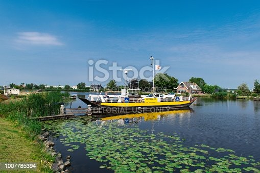 The small ferry at Nessersluis ferries pedestrians, cyclists, motors and even cars across the river Amstel between Uithoorn and Amstelveen in The Netherlands.