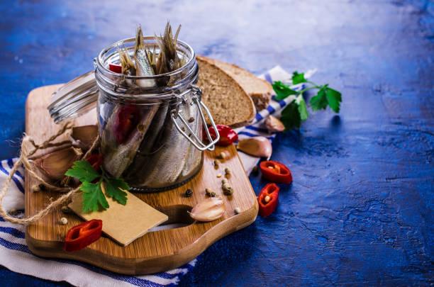 kleine fische in salzlake - silberzwiebeln stock-fotos und bilder