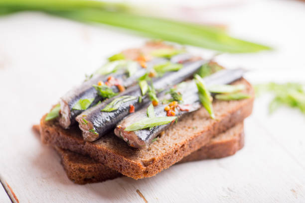 Small fish of sprat with spices on a piece of dark bread stock photo