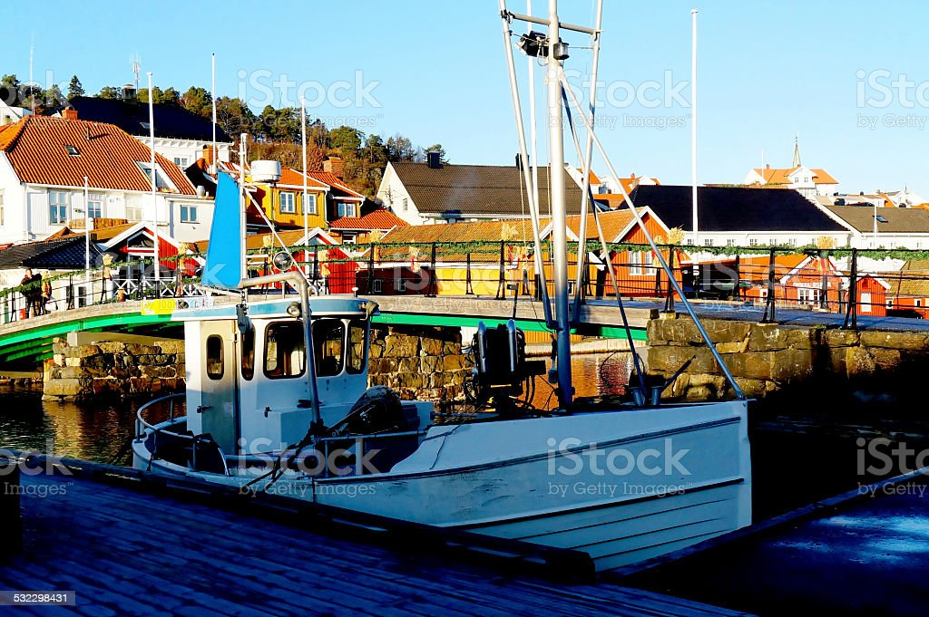 Small fishing boat anchored in the port stock photo