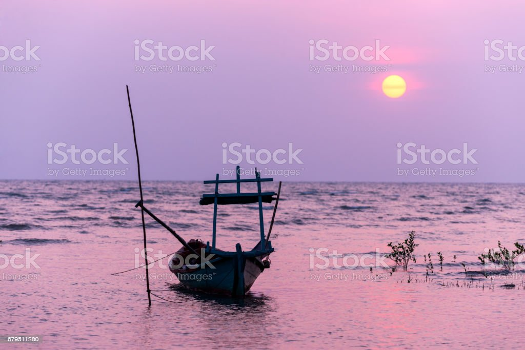 Small fishing boat at sunset in the sea royalty-free stock photo