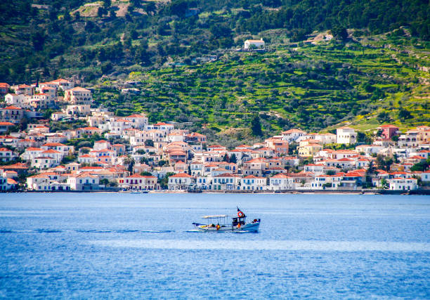 small fishing boat crossing the blue waters opposite the beautiful island of Spetses, located in Saronikos gulf near Athens city, Greece. stock photo