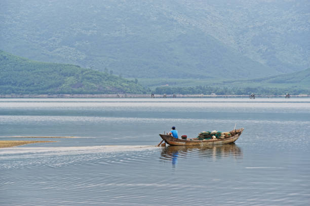 Small fishing boat floating on the lake against mountains. Lang Co, Vietnam stock photo