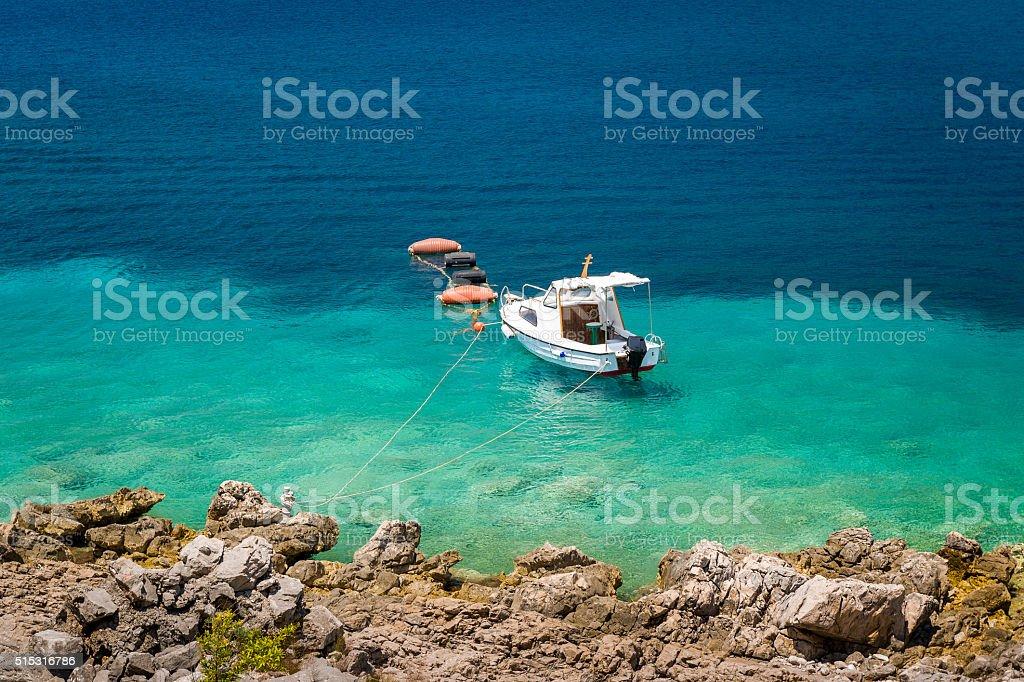 Small fishing boat moored at paradise bay shore stock photo