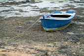 small fishing boat moored in the sand