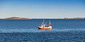 Small fishing boat is in Norwegian sea, Trondheim region, Norway