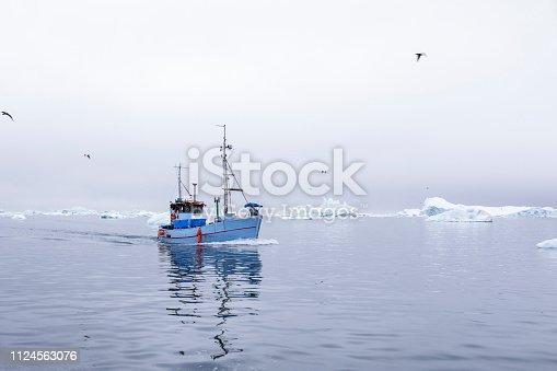 Icy sea near Greenland and a small fishing ship sailing
