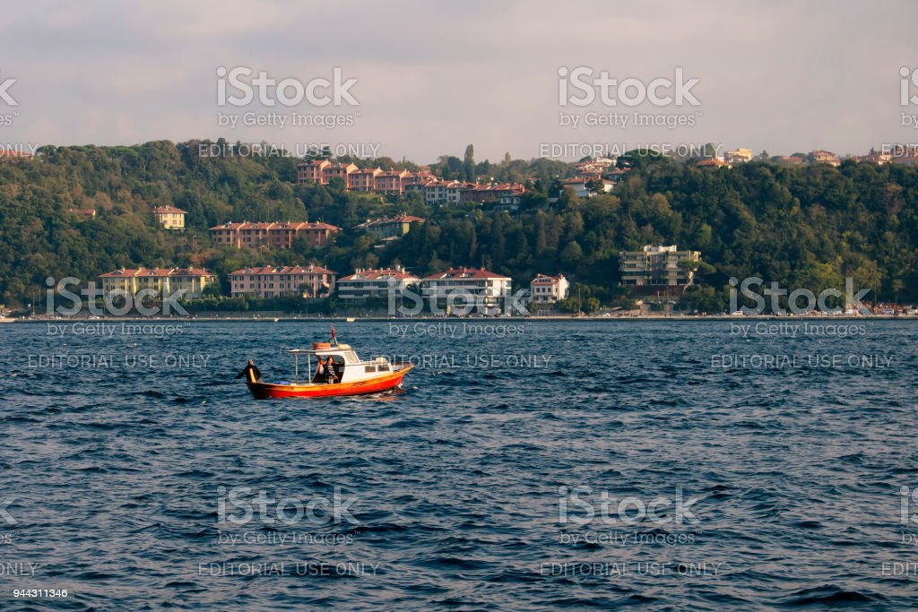 Small fishing boat on Bosphorus strait in Istanbul. Asian side is in the  background. - Stock image .