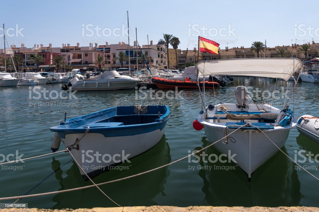 Small fishing boats moored against the harbor wall, in southern Spain, in the summer. The Spanish flag can be seen in the backgorund stock photo
