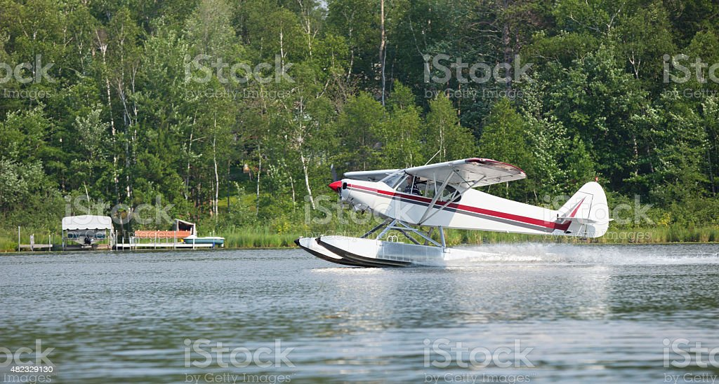 Small floatplane lands on a Minnesota lake stock photo