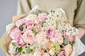 European floral shop. Two Beautiful bouquets of mixed flowers in womans hands. the work of the florist at a flower shop. Delivery fresh cut flower
