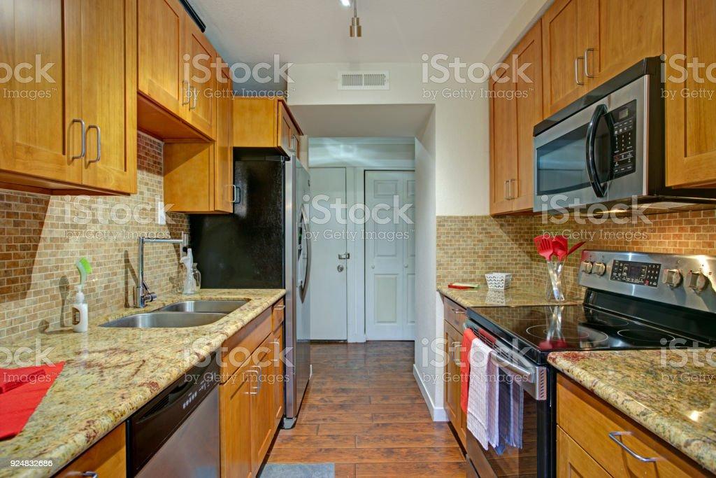 Small Galley Kitchen Design With Black Kitchen Appliances Stock