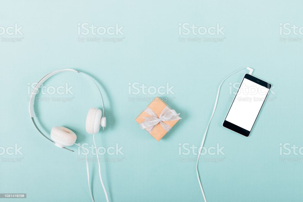 Small gift box near white headphones and connected smart phone with...